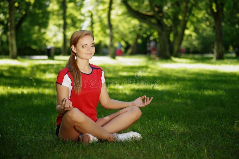 Yogakvinnan som in mediterar, parkerar fotografering för bildbyråer