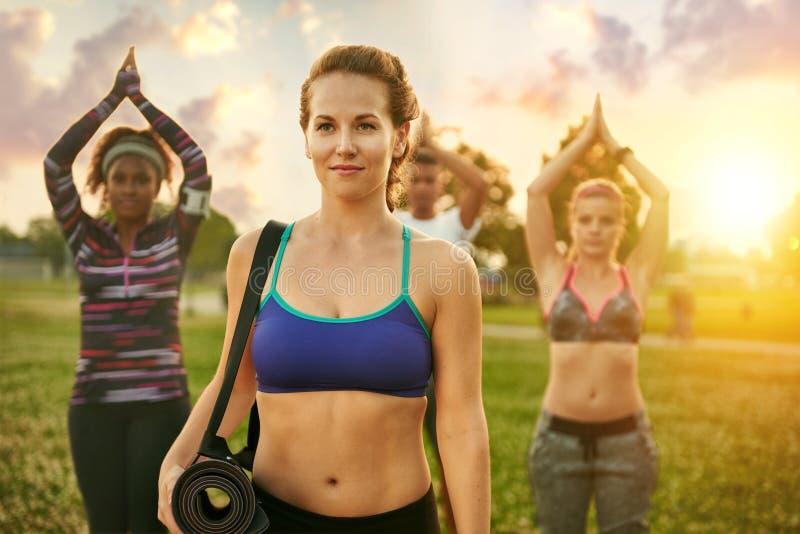 Yogalärare som framme står av hennes grupp, medan rymma henne matt på gräset på solnedgången i natur parkera arkivbild