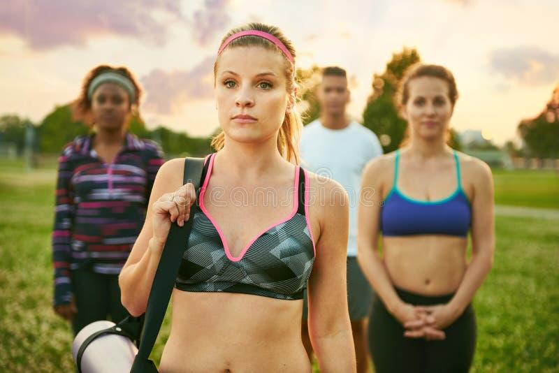 Yogalärare som framme står av hennes grupp, medan rymma henne matt på gräset på solnedgången i natur parkera arkivfoton