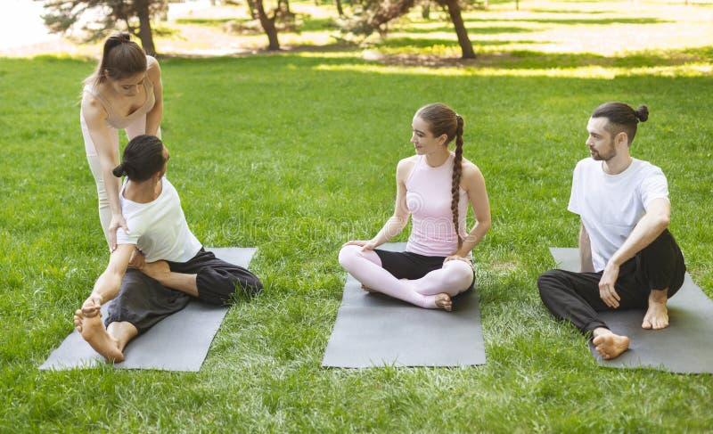 Yogalärare som hjälper den unga mannen att sträcka muskler under övning arkivbild