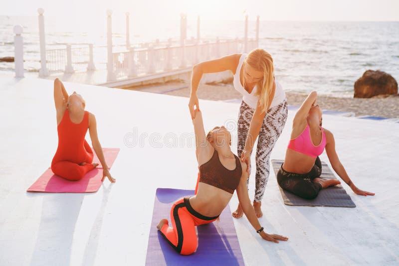 Yogaläraren visar flickorna hur man gör korrekt posera royaltyfria bilder