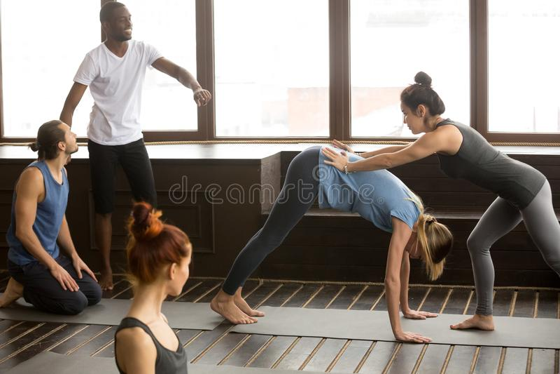 Yogalehrer, der die Frau tut abwärtsgerichtetes Hund-stretchin unterstützt stockfoto
