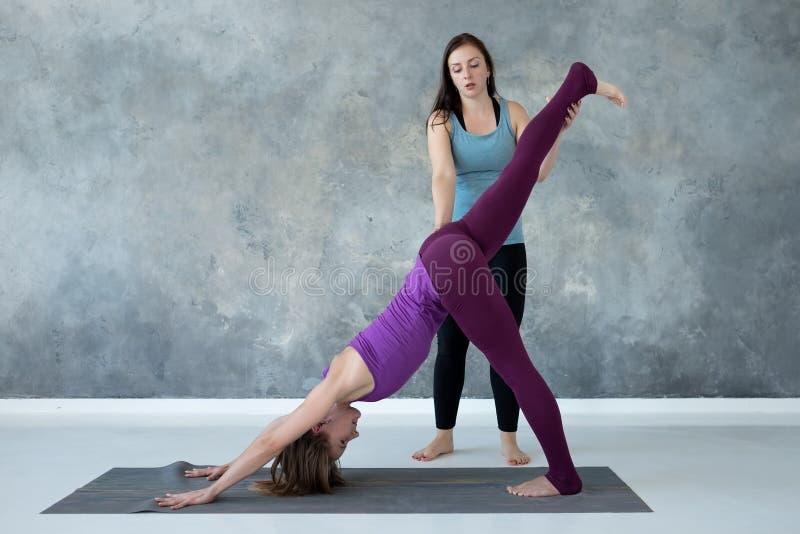 Yogalehrer, der ihrem Studenten hilft, Muskeln holdingher Bein auszudehnen lizenzfreies stockbild