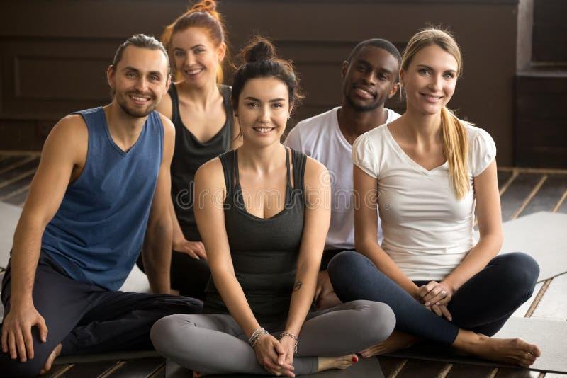 Yogalehrer, der mit gemischtrassigen Leuten am Gruppentraining aufwirft lizenzfreie stockfotos