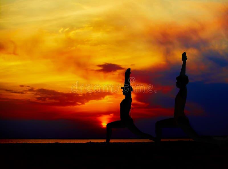 Yogaleute, die draußen in der Kriegershaltung durch Strand bei Sonnenaufgang oder Sonnenuntergang ausbilden und meditieren stockfotos