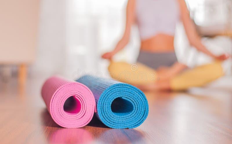Yogamatten op houten vloer en vaag vrouwelijk lichaam bij de achtergrond stock foto