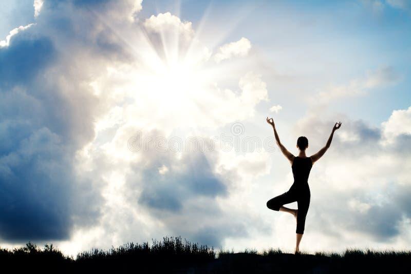 Yogameditation, kvinnaställning med lyftta armar, natursolhimmel royaltyfria bilder