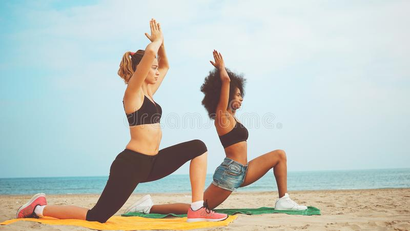 Yogameisjes op strand het meisje van het afrohaar en de blonde meisje meditatie van de opleidingsyoga samen aan de overzeese kant stock foto's