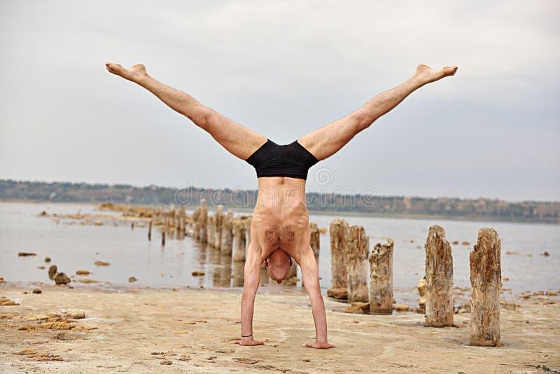 Yogamens die zich op handen bevinden stock foto
