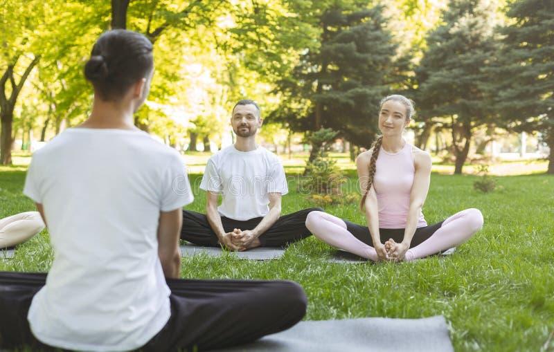 Yoganybörjare som lyssnar till instruktören som sitter i Lotus, poserar arkivbild
