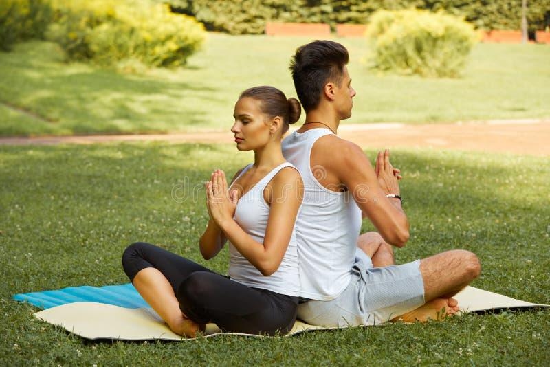 Yogaoefening Jong paar die in geschiktheidsclub mediteren stock foto's