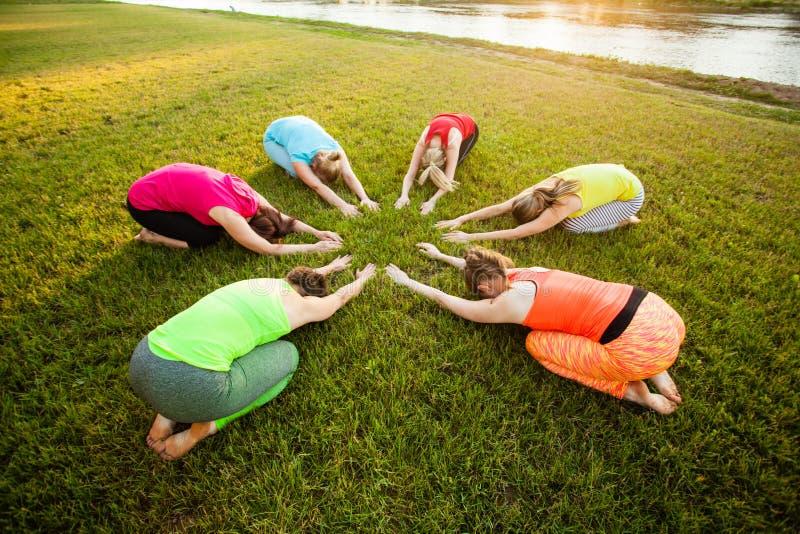 Yogapraktijk op het groene gebied royalty-vrije stock afbeeldingen