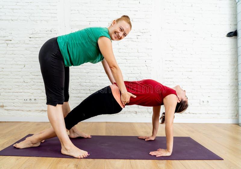 Yogaterapeuten som hjälper den unga studenten som sträcker i yogaövning, poserar i sunt livsstilbegrepp royaltyfria foton
