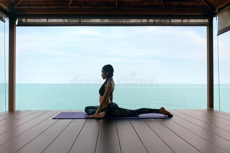 Yogatraining Frau im Sport kleidet das Ausdehnen des Körpers nahe Meer lizenzfreies stockfoto