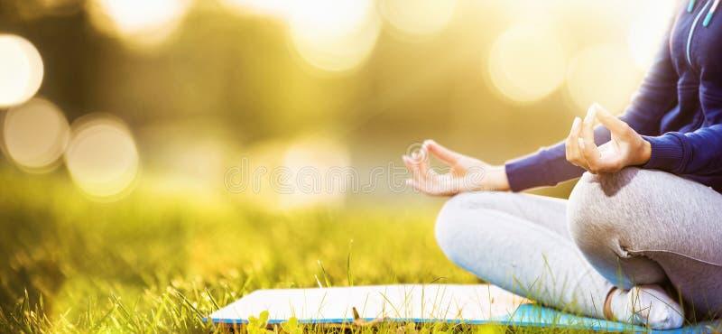 Yogavrouw die bij zonsondergang mediteren stock fotografie