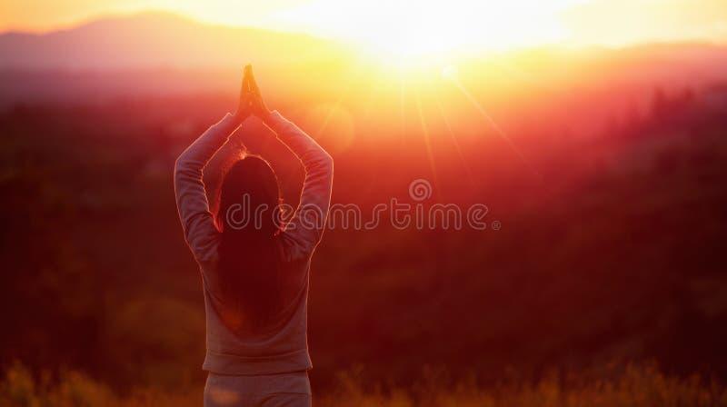 Yogavrouw die bij zonsondergang mediteren stock foto's