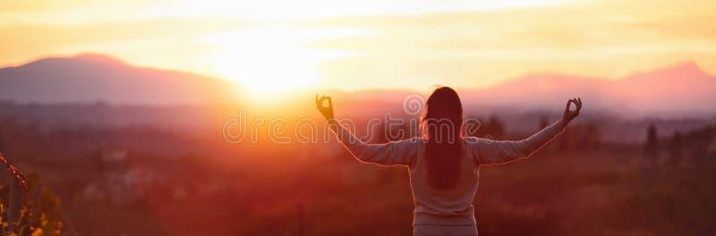 Yogavrouw die bij zonsondergang mediteren royalty-vrije stock foto's
