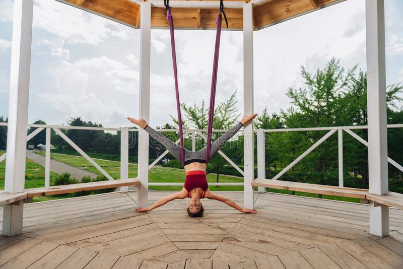 Yogavrouw die grijze beenkappen dragen die zich op hoofd bevinden die vliegyoga doen stock foto