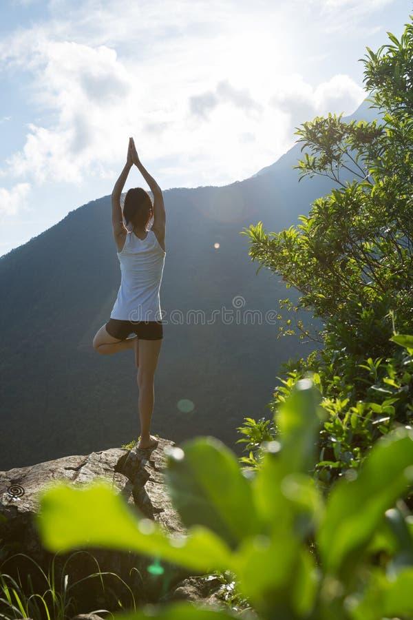 Yogavrouw die op rand van de berg de piekklip mediteren stock afbeeldingen