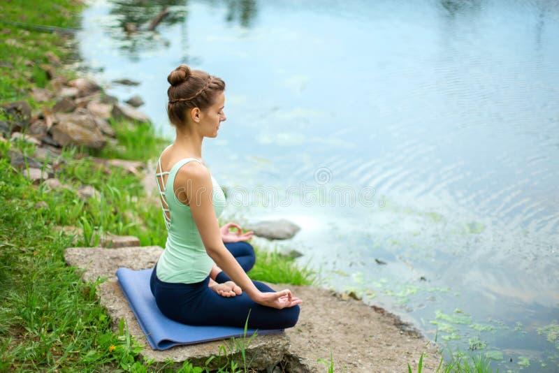 Yogavrouw het praktizeren de yogales, ademhaling die, meditatie, oefening Ardha Padmasana doen, halve lotusbloem stelt met mudrag royalty-vrije stock afbeelding
