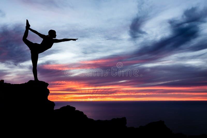 Yogavrouw, oceaan en zonsondergang