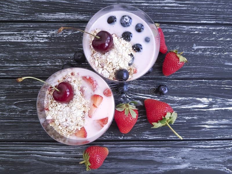 Yoghurt, aardbei, kers, het glas van de ochtendbosbes op een zwarte houten achtergrond royalty-vrije stock afbeelding