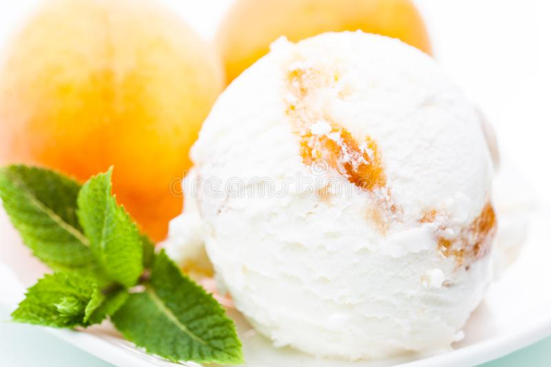 Yoghurt - apricot ice cream scoop with apricot and mint leafs. 