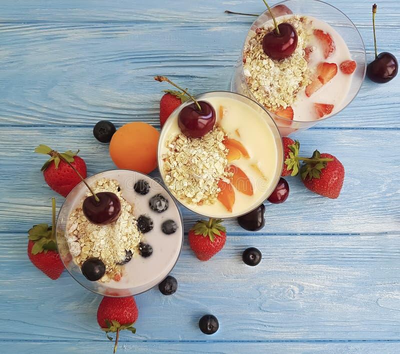 yoghurt, de kers van de de aardbeiabrikoos van de havermeelbosbes op een blauwe houten achtergrond royalty-vrije stock foto