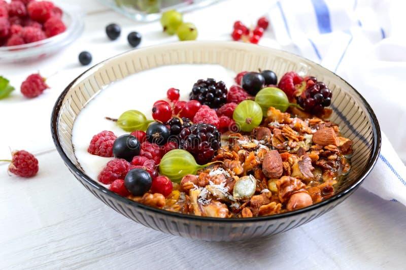 Yoghurt, granola, verse bessen in een kom op een witte houten achtergrond Heerlijke en gezonde ontbijt Juiste voeding dieet royalty-vrije stock afbeeldingen