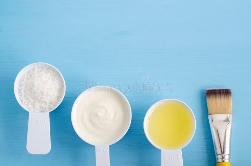 Yoghurt, kokosflingor och olivolja för gräddfil grekisk i små skopor Ingredienser för att förbereda diy maskeringar, skurar, mois arkivfoton