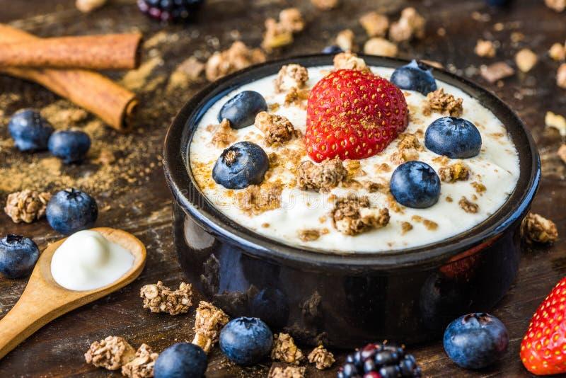 Yoghurt med jordgubben, blåbär och mysli arkivfoto