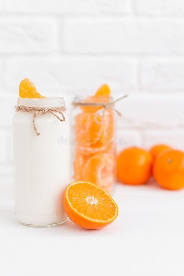 Yoghurt med nya orange skivor och hela apelsiner arkivbilder
