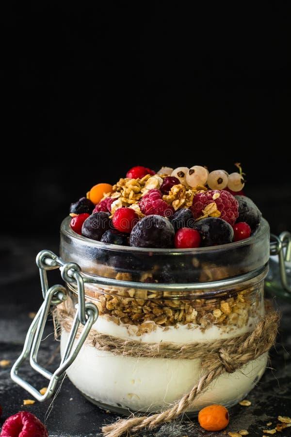 Yoghurt met granola en bessen in kleine kruik, aardbeien, bosbessen , zwarte bes zoetheid Eigengemaakte yoghurt Gezond voedsel royalty-vrije stock foto