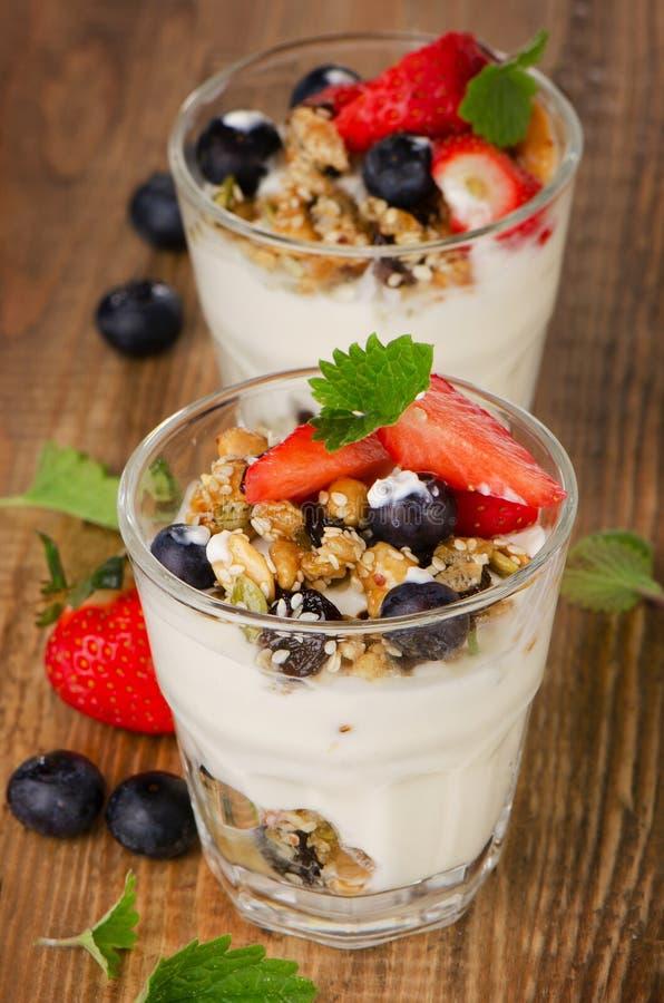 Yoghurt met Granola en verse bessen op houten achtergrond royalty-vrije stock afbeelding