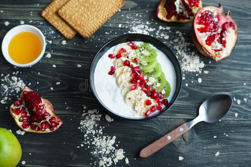 Yoghurt smoothie bowl with kiwi and banana slices, oatmeal and p. Omegranate. Healthy diet meal for breakfast stock image