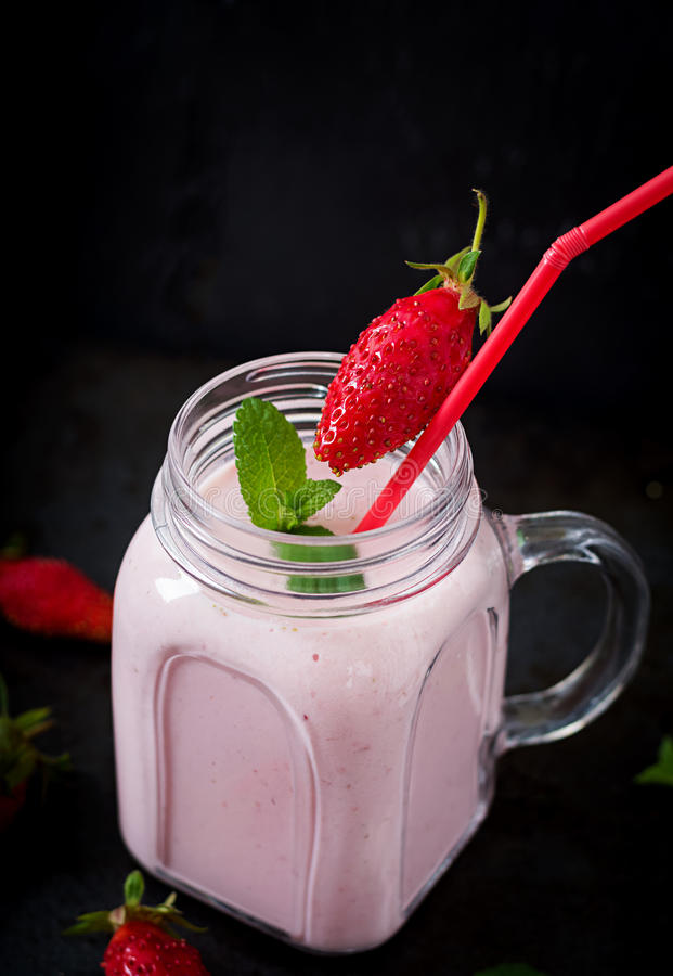 Yoghurt-strawberry smoothies in a jar. On a black background stock photography