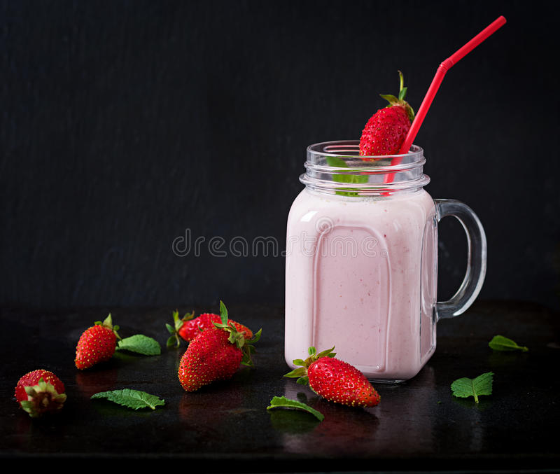 Yoghurt-strawberry smoothies in a jar. On a black background royalty free stock image
