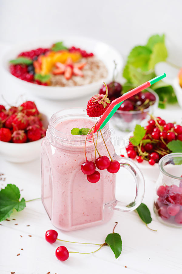 Yoghurt-strawberry smoothies in a jar. On a white background royalty free stock photos