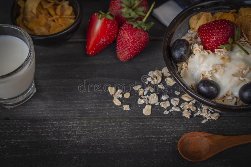 Yoghurtblandninghavremjölet, jordgubben och druvatoppning i svart bunke på trätabellen med skeden, jordgubbe, mjölkar i exponerin arkivbilder