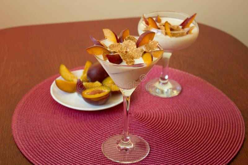 Yoghurtefterrätt med plommoner och veteflingor Sund efterrätt med arkivfoton