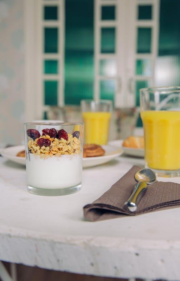 Yoghurten med granola och bär tjänade som i exponeringsglas arkivbilder