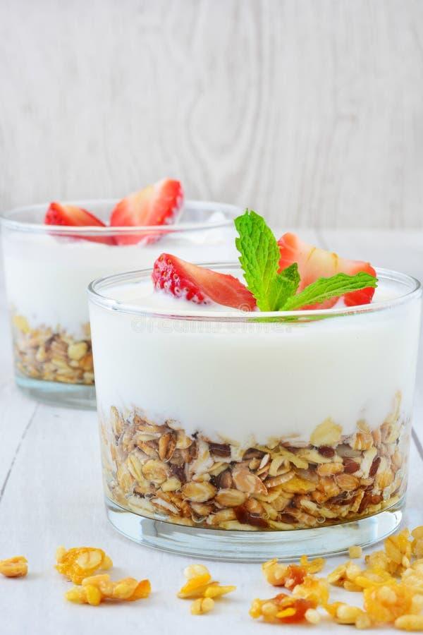 Yoghurter som är glass med sädesslag och jordgubbar, frukost royaltyfria bilder