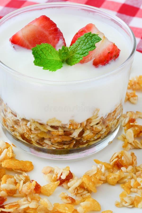 Yoghurter som är glass med sädesslag och jordgubbar, frukost arkivbild