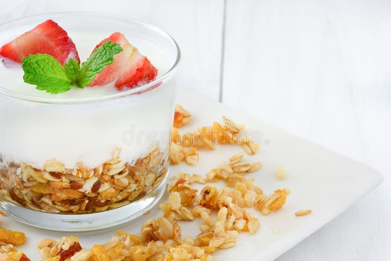 Yoghurter som är glass med sädesslag och jordgubbar, frukost royaltyfria foton