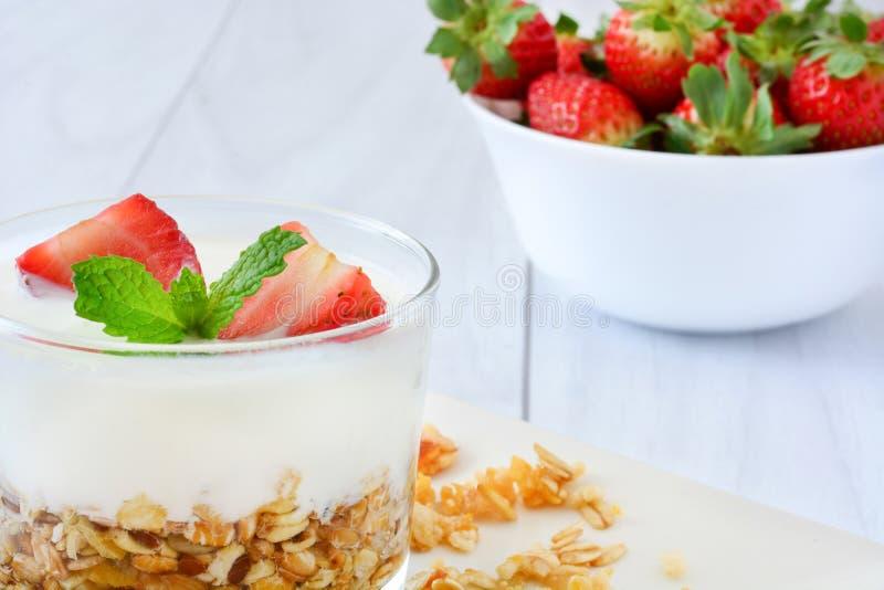 Yoghurter som är glass med sädesslag och jordgubbar, frukost arkivfoto