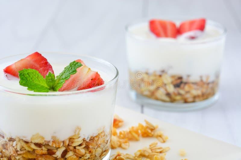 Yoghurter som är glass med sädesslag och jordgubbar, frukost arkivfoton