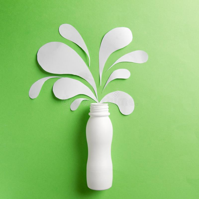 Yoghurtflaska med färgstänk royaltyfria foton
