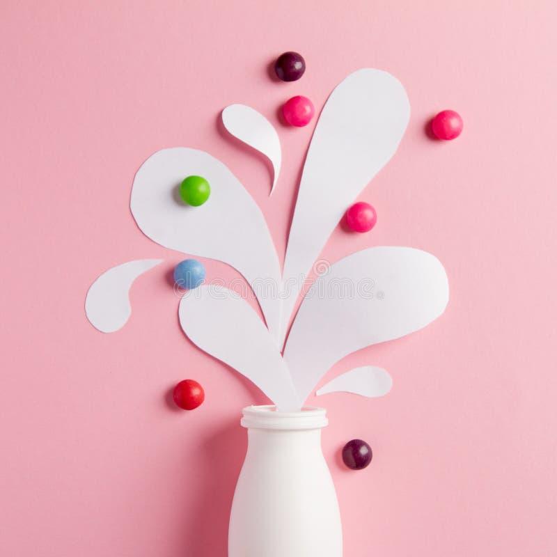 Yoghurtflaska med färgstänk och vitaminer arkivbilder