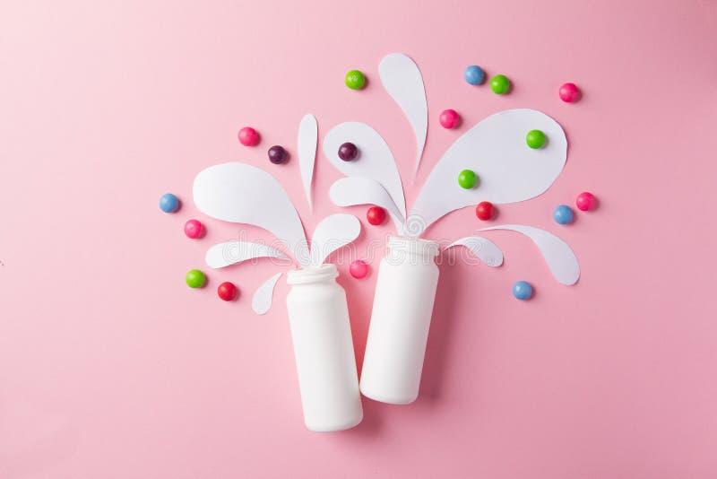 Yoghurtflaska med färgstänk och vitaminer arkivfoton
