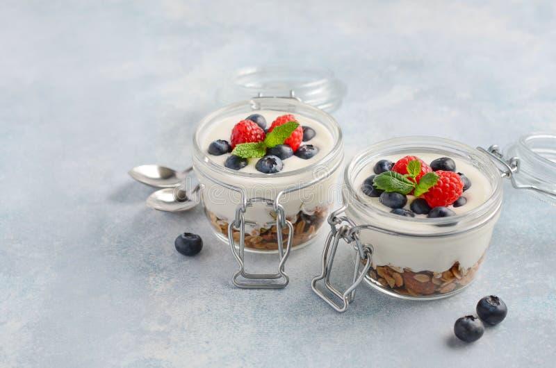 Yoghurtparfait met eigengemaakte granola en verse bessen in een glaskruiken op blauwe concrete achtergrond, gezond ontbijtconcept stock fotografie